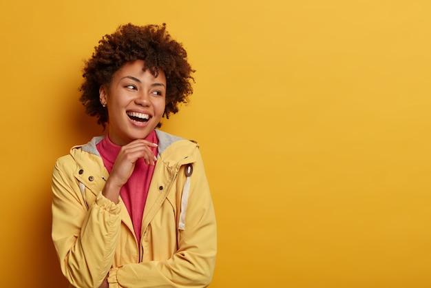 Die aufnahme einer hübschen sorglosen frau hält die hand unter dem kinn, schaut zur seite, trägt eine jacke, posiert an der gelben wand und bietet platz für ihre werbeinhalte. emotions- und gefühlskonzept