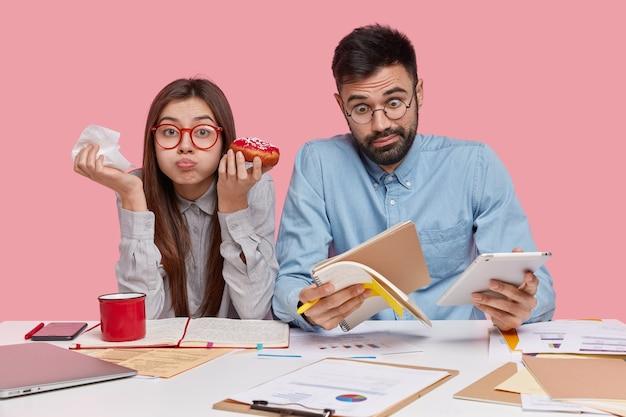 Die aufnahme einer lustigen brünetten frau isst einen köstlichen donut, hat vollen mund, während ihr partner schockierende neuigkeiten erkennt, auf den notizblock starrt und das touchpad hält