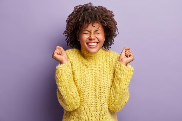 Die aufnahme einer überglücklichen schwarzen frau feiert eine wundervolle leistung, hat erfolg, trägt einen gelben pullover, zeigt weiße zähne, hat ein zahniges lächeln und zeigt auf eine lila wand. feierkonzept