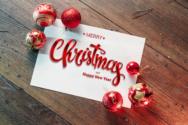 Die aufschrift von frohen weihnachten, dekorationen, blatt a4 auf einer hölzernen braunen tabelle. weihnachtskarte, urlaub. gemischte medien.