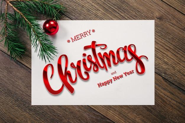 Die aufschrift von frohen weihnachten, grüne fichtenzweige, dekorationen, blatt a4 auf einer hölzernen braunen tabelle. weihnachtskarte, urlaub. gemischte medien.