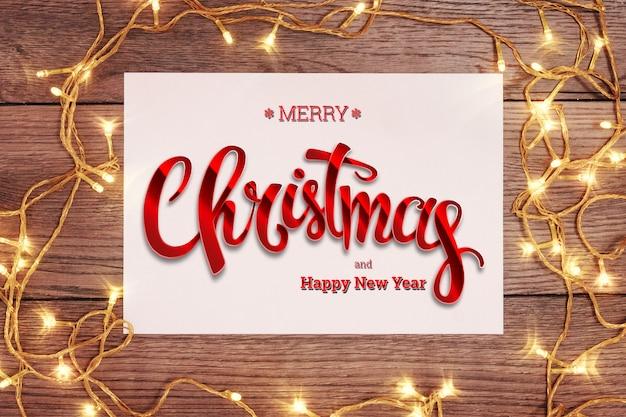 Die aufschrift von frohen weihnachten und von girlande auf einer hölzernen braunen tabelle. weihnachtskarte, urlaub. gemischte medien.