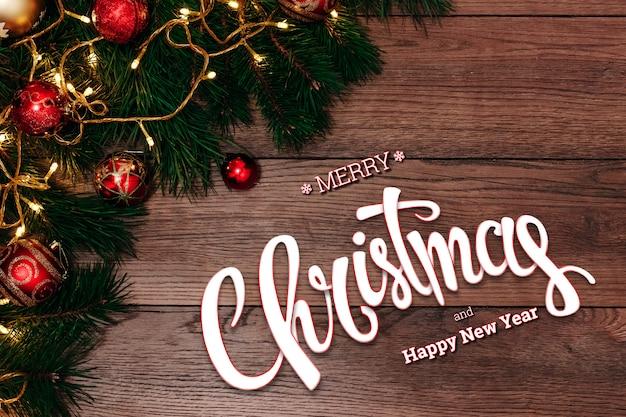 Die aufschrift von frohen weihnachten, von grüner fichte und von hackenden niederlassungen auf einer hölzernen braunen tabelle. weihnachtskarte, urlaub. gemischte medien.