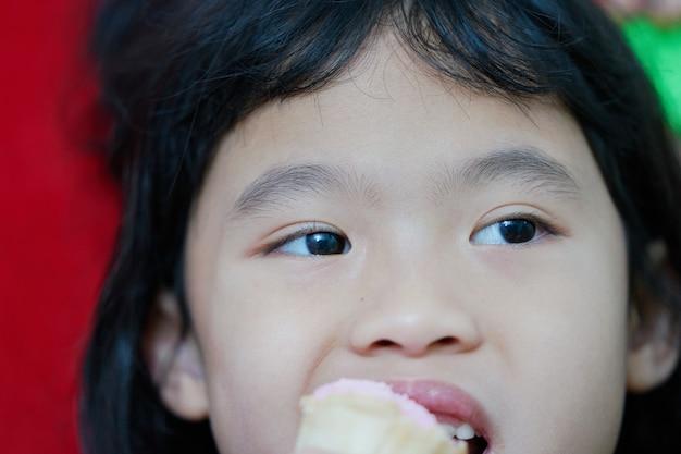Die augen des jungen mädchens schlossen sich, während sie aß und etwas betrachtete