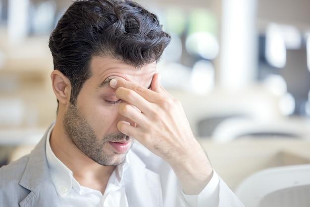 Die augen eines müden jungen mannes sind müde von der computerarbeit