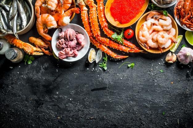 Die auswahl an verschiedenen meeresfrüchten. auf schwarzem rustikalem hintergrund