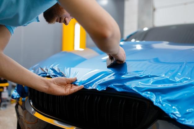 Die autoverpackung bringt schutzfolie oder folie auf die motorhaube