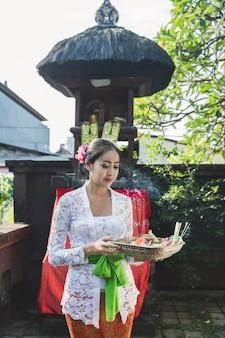 Die balinesische frau betet und opfert canang sari im tempel