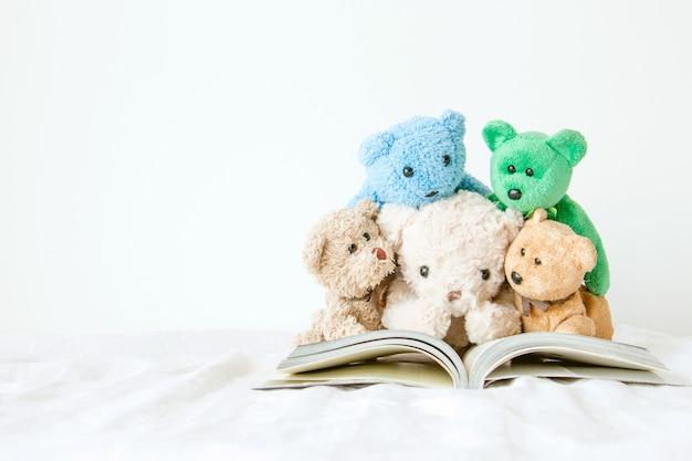 Die bande des teddybären mit einem buch, das sie für die prüfung lesen müssen