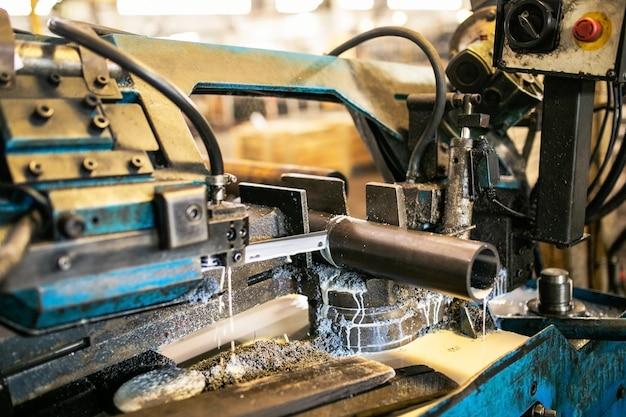 Die bandsägemaschine schneidet rohmetallstangen mit der kühlflüssigkeit.