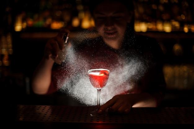 Die barkeeperin fügt einem alkoholischen cocktail einen duftenden erbsenwhisky hinzu