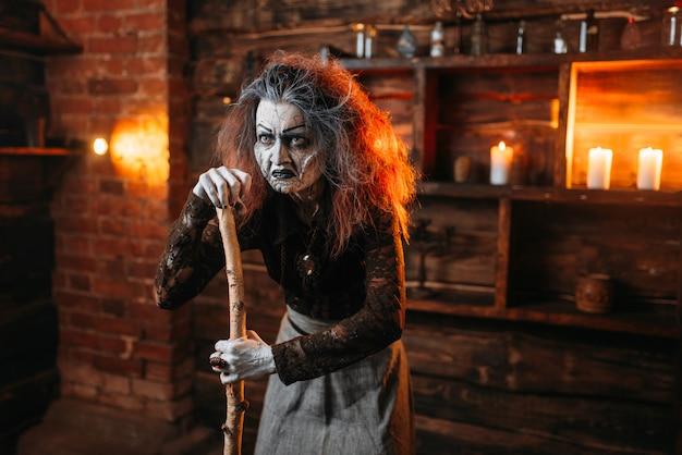 Die beängstigende hexe steht auf einem stock und liest den zauber, die spirituelle seance. die weibliche voraussagerin nennt die geister eine schreckliche wahrsagerin