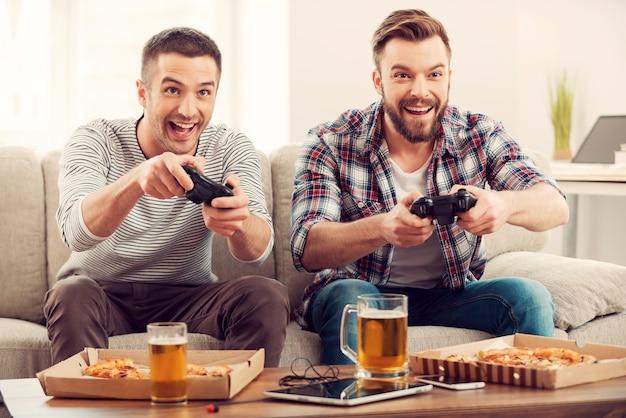 Die begeisterten spieler. zwei junge glückliche männer, die videospiele spielen, während sie auf dem sofa sitzen