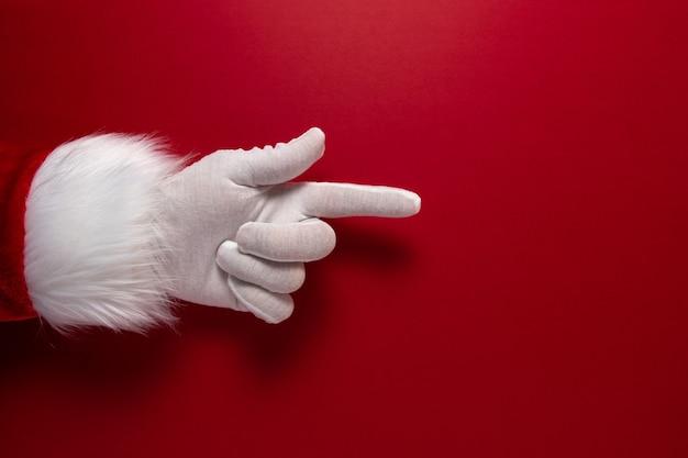 Die behandschuhte hand des weihnachtsmanns zeigt auf eine geste