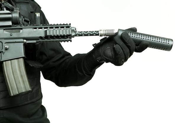 Die behandschuhte hand eines mannes befestigt einen schalldämpfer am lauf eines maschinengewehrs