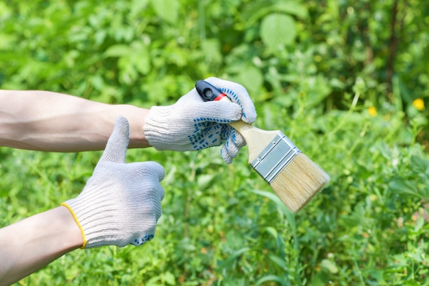 Die behandschuhte hand eines mannes hält einen breiten pinsel zum malen auf einem grün.