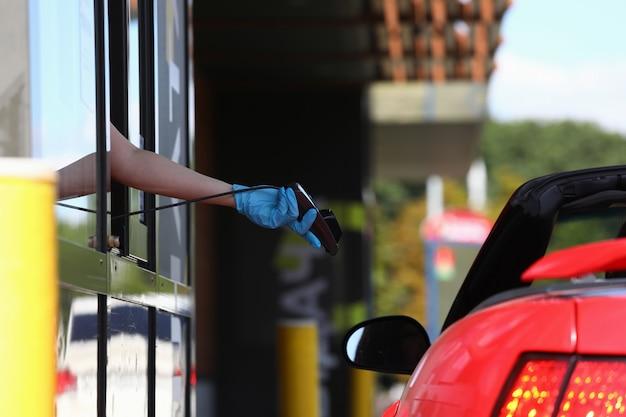 Die behandschuhte hand hält das pos-terminal und hält es in richtung auto