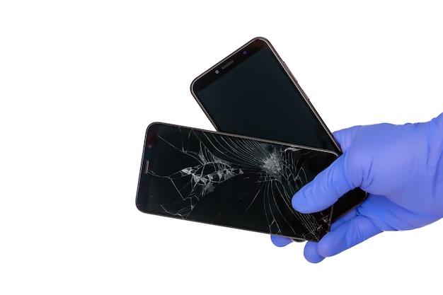Die behandschuhte hand hält ein kaputtes smartphone mit einem zerbrochenen handybildschirm und einem neuen handybildschirm auf einem weißen feld