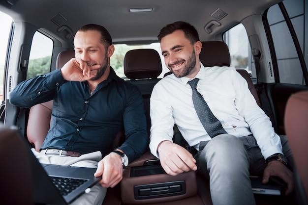 Die beiden alten geschäftsfreunde schließen eine neue vereinbarung in einem informellen rahmen im innenraum des autos