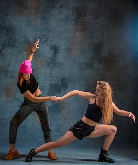 Die beiden attraktiven mädchen tanzen im studio
