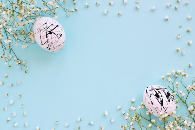 Die beiden eier sind weiß mit schwarzen flecken und blumen auf blauem grund mit einer kopie des raumes. ostern. minimalismus. festlicher hintergrund. postkarte. rahmen