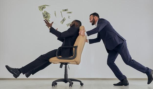 Die beiden geschäftsleute, die mit stuhl spielen und geld werfen