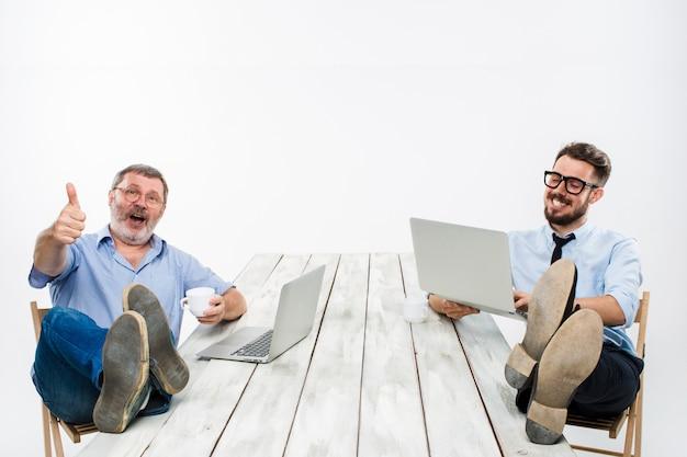 Die beiden geschäftsleute mit den beinen über dem tisch arbeiten an laptops