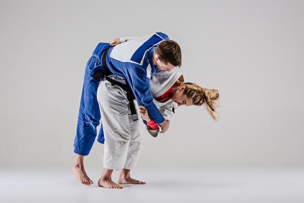 Die beiden judokas-kämpfer posieren auf grau