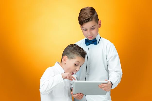 Die beiden jungen benutzen einen laptop auf orangefarbenem raum