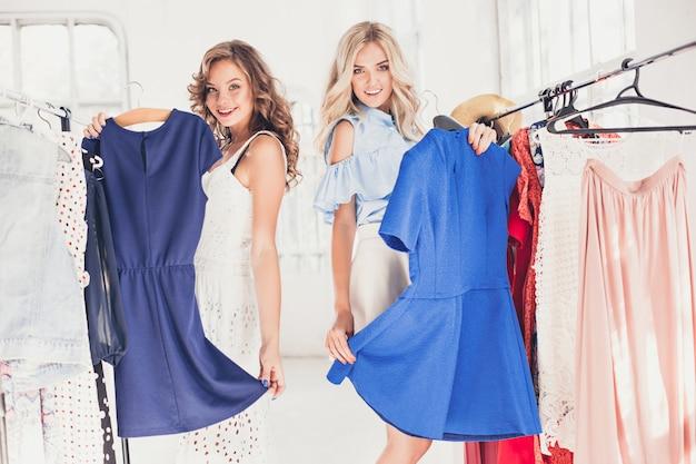 Die beiden jungen hübschen frauen schauen sich kleider an und probieren sie an, während sie im geschäft wählen