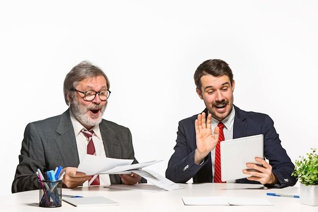 Die beiden kollegen arbeiten im büro auf weiß zusammen.