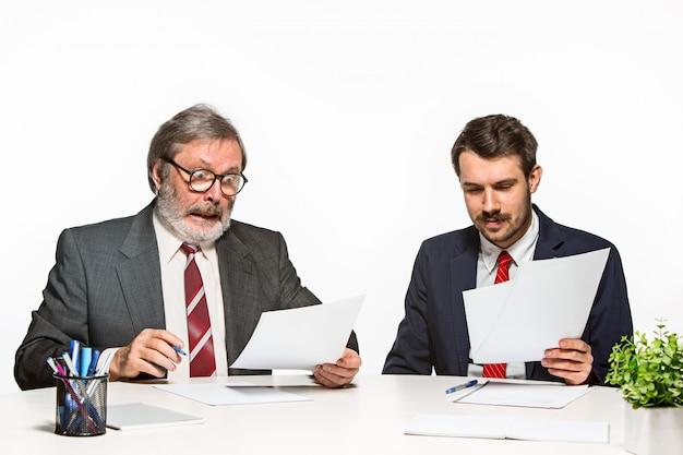 Die beiden kollegen arbeiten im büro im weißen studio zusammen