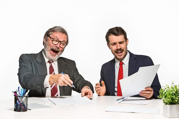 Die beiden kollegen arbeiten im büro zusammen.