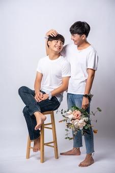 Die beiden männer, die sich liebten, hielten den kopf und setzten sich auf einen stuhl.