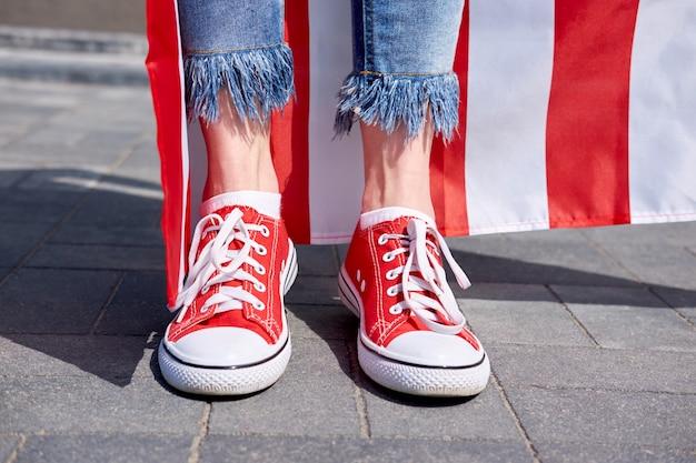 Die beine der frau in den stilvollen jeans und in der roten amerikanischen flagge der turnschuhe auf hintergrund