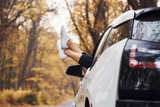 Die beine der frau sind aus dem autofenster. modernes brandneues auto im wald.
