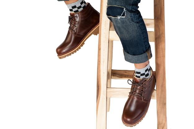 Die beine der modemänner in den jeans und in braunen stiefeln lokalisiert.