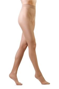 Die beine der perfekten frau in der beige strumpfhose lokalisiert auf weiß