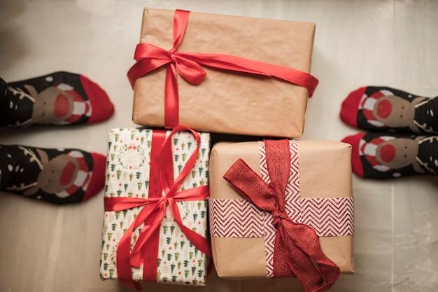 Die beine der person in weihnachtssocken in der nähe von präsentkartons