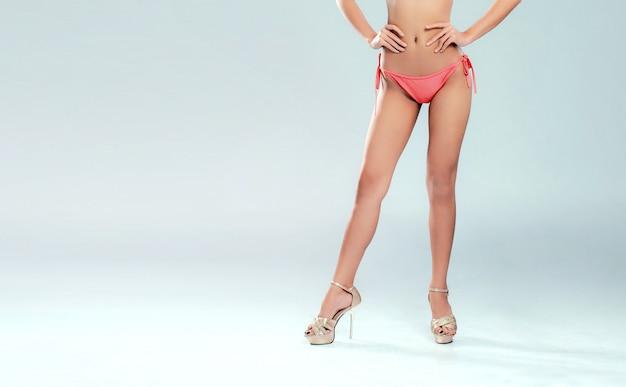 Die beine der sexy frau im rosa bikini