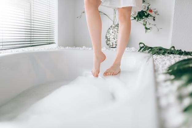 Die beine der weiblichen person tauchen mit schaum in die badewanne ein. badezimmerinnenraum mit fenster