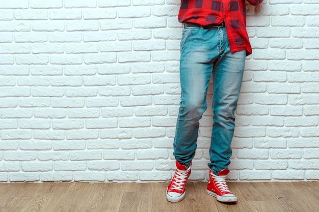Die beine des jungen modemannes in den jeans und in den turnschuhen auf bretterboden