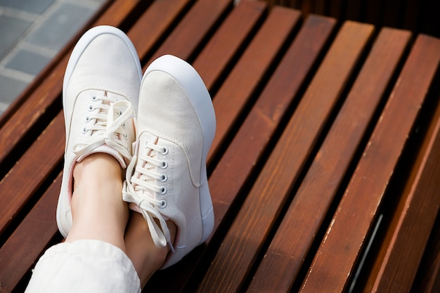Die beine des mädchens in neuen weißen turnschuhen und jeans