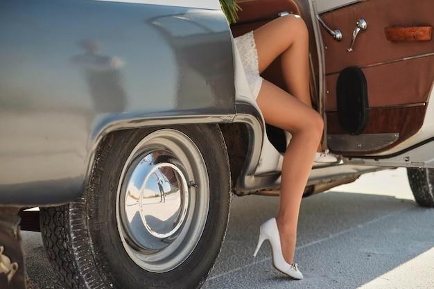 Die beine des mädchens verlassen ein altes auto. junge frau in schuhen mit hohen absätzen