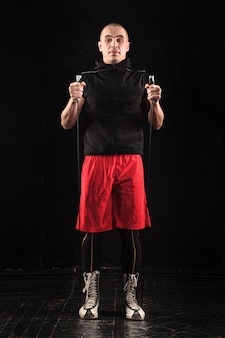 Die beine des muskulösen mannes mit springseil