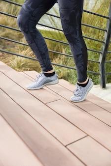 Die beine des weiblichen läuferathleten, der treppe in der städtischen stadt tut herz-sport-training hinaufgeht, laufen während des sommers