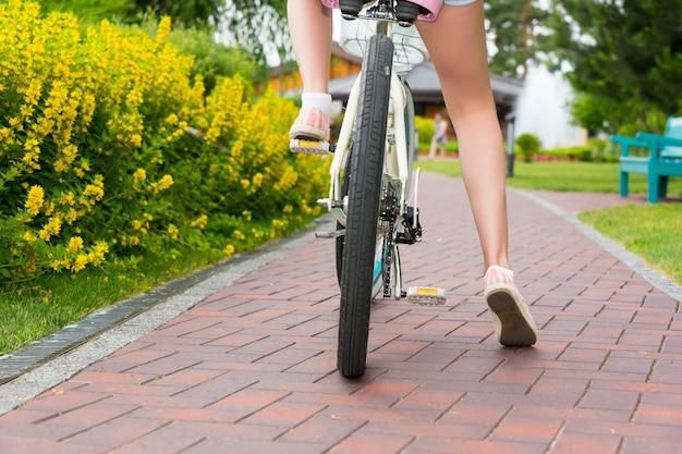 Die beine einer frau begannen mit dem fahrrad auf einem fußweg in einem park