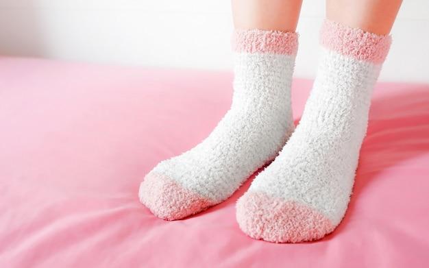 Die beine einer schönen frau tragen warme socken im schlafzimmer. mode rosa socken in gemütlichen.