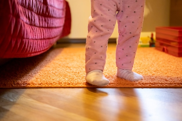 Die beine eines kleinen kindes laufen durch den raum. konzept der ersten schritte des babys. kein gesicht. glückliche elternschaft