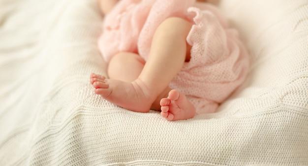 Die beine eines neugeborenen babys eingewickelt in einer rosa decke, die auf einer weißen gestrickten decke liegt. tiefenschärfe.